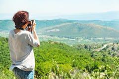 Punto di vista posteriore di un fotografo della donna che prende le immagini della valle con le montagne da sopra immagini stock