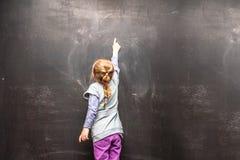 Punto di vista posteriore di una bambina che ponting a qualcosa su una lavagna Immagini Stock Libere da Diritti