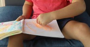 Punto di vista potato del bambino sveglio che attinge carta con le matite mentre trovandosi sul pavimento archivi video