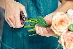 Punto di vista potato del fiorista che fa mazzo fresco Condizione femminile dei fiori da taglio al contatore Floreale, studio del fotografia stock libera da diritti