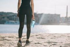 punto di vista potato della sportiva con acqua in bottiglia che cammina sulla spiaggia fotografie stock libere da diritti