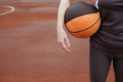 Punto di vista potato di una giovane donna in abiti sportivi che tengono una pallacanestro immagine stock libera da diritti