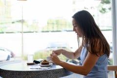 Punto di vista di profilo di giovane bella donna di affari che mangia dolce dalla finestra fotografie stock