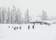 Punto di vista scenico di piccola gente intorno alla stazione sciistica quando giorno nevoso Immagini Stock