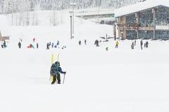 Punto di vista scenico di piccola gente intorno alla stazione sciistica quando giorno nevoso Fotografia Stock