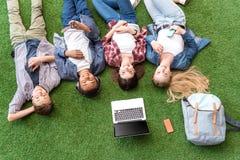 punto di vista sopraelevato del gruppo multietnico di adolescenti sorridenti con la menzogne digitale dei dispositivi immagini stock