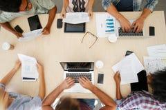 Punto di vista sopraelevato del personale con i dispositivi di Digital nella riunione immagine stock