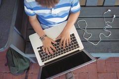 Punto di vista sopraelevato del ragazzo che per mezzo del computer portatile Immagine Stock Libera da Diritti