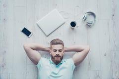 Punto di vista sopraelevato dell'uomo calmo in abbigliamento casuale che si trova sul pavimento Fotografia Stock