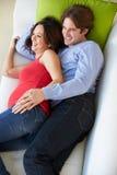 Punto di vista sopraelevato dell'uomo e della moglie incinta che guardano TV sul sofà immagini stock
