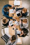 punto di vista sopraelevato delle persone di affari sulla riunione alla tavola con le tazze di caffè digitali dei dispositivi fotografia stock libera da diritti