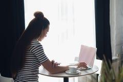 Punto di vista sopraelevato di una donna esecutiva che scrive in suo computer portatile Vista dal retro di una seduta femminile a fotografie stock