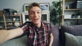 Punto di vista sparato del giovane bello con il fronte espressivo che fa il video dispositivo di tenuta online di chiamata che pa stock footage