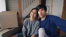Punto di vista sparato del marito adorabile e della moglie delle coppie che fanno video chiamata online dopo la rilocazione Stann stock footage