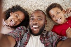 Punto di vista sparato del padre And Children Posing per Selfie fotografia stock