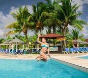 Punto di vista splendido della bambina allegra felice che salta nella piscina tropicale Fotografie Stock