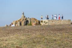 Punto di vista di struttura dell'erba nella prospettiva, della sfuocatura del fondo con roccia e della gente, vicino al mare fotografie stock libere da diritti