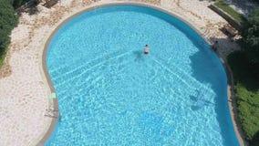 Punto di vista superiore aereo dell'uomo di nuoto in stagno all'aperto, concetto tropicale del movimento lento di festa di vacanz archivi video