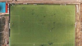Punto di vista superiore aereo della gente che gioca a calcio sul campo di erba verde il giorno di estate video d archivio