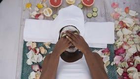 Punto di vista superiore di bella giovane donna africana in asciugamano bianco sulla testa che si trova con i pezzi di cetriolo s video d archivio