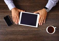 Punto di vista superiore da tavolino di legno dei pantaloni a vita bassa d'annata, mani maschii facendo uso del computer portatil Immagine Stock