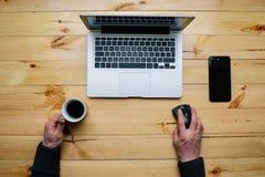 Punto di vista superiore da tavolino di legno dei pantaloni a vita bassa d'annata, mani maschii facendo uso di un computer portat immagini stock libere da diritti