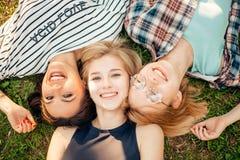 Punto di vista superiore degli amici alla moda che esaminano macchina fotografica e che sorridono mentre trovandosi sull'erba Fotografie Stock Libere da Diritti