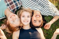 Punto di vista superiore degli amici alla moda che esaminano macchina fotografica e che sorridono mentre trovandosi sull'erba Fotografia Stock