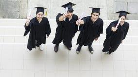 Punto di vista superiore degli studenti della gente con gli abiti ed il cappello di graduazione Fotografia Stock Libera da Diritti