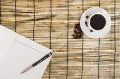 Punto di vista superiore dei chicchi di caffè con la tazza bianca, il taccuino in bianco e la penna sulla stuoia Immagini Stock Libere da Diritti