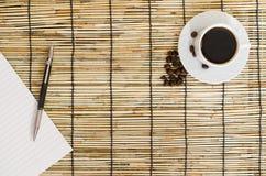 Punto di vista superiore dei chicchi di caffè con la tazza bianca, il taccuino in bianco e la penna sulla stuoia Fotografia Stock Libera da Diritti