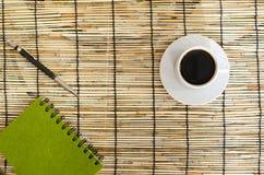 Punto di vista superiore dei chicchi di caffè con la tazza bianca, il taccuino verde e la penna sulla stuoia Immagini Stock