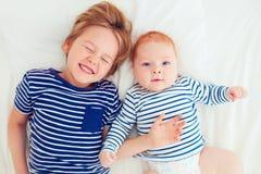 Punto di vista superiore dei fratelli divertendosi che si trova a letto a casa Fotografia Stock