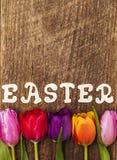 Punto di vista superiore dei tulipani e parola Pasqua sulla tavola di legno Fotografia Stock