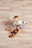 Punto di vista superiore del bambino felice che gioca con i giocattoli variopinti sul pavimento Fotografie Stock Libere da Diritti