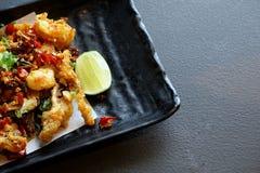 Punto di vista superiore del calamaro fritto con il peperoncino rosso ed il limone in banda nera fotografie stock