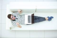 Punto di vista superiore del giovane emozionante che utilizza il suo computer portatile nella vita luminosa Fotografia Stock Libera da Diritti