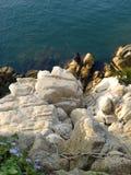 Punto di vista superiore del pescatore che si siede sulle rocce con le canne da pesca fotografia stock