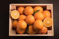 Punto di vista superiore dell'arancia dolce matura in scatola di legno isolata su fondo nero Immagini Stock