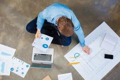 Punto di vista superiore dell'ingegnere che studia i grafici e modello sul pavimento Immagine Stock