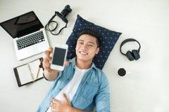 Punto di vista superiore dell'uomo asiatico che si trova sul pavimento con il computer portatile, macchina fotografica, tum Fotografie Stock Libere da Diritti