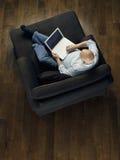 Punto di vista superiore dell'uomo calvo che per mezzo del computer portatile sul sofà immagine stock libera da diritti