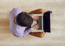Punto di vista superiore dell'uomo che si siede sul pavimento e che lavora con un computer portatile Fotografie Stock Libere da Diritti