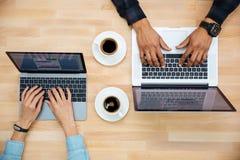 Punto di vista superiore dell'uomo e della donna che lavorano con due computer portatili Fotografia Stock