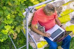 Punto di vista superiore dell'uomo di eldery che si siede e che si rilassa sul rasort di vacanza estiva facendo uso del computer  immagine stock libera da diritti