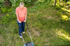 Punto di vista superiore dell'uomo senior che per mezzo della falciatrice da giardino sul campo di erba fotografie stock