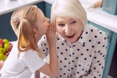 Punto di vista superiore della bambina che divide il suo segreto con la nonna fotografia stock libera da diritti