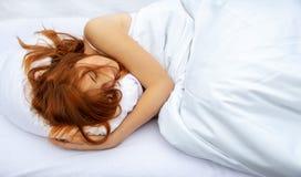 Punto di vista superiore della donna attraente, giovane, dai capelli rossi che si rilassa a letto abbracciando un cuscino bianco  fotografia stock