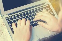 Punto di vista superiore della donna che si siede nel parco sull'erba verde con il computer portatile, mani sulla tastiera Il pri Fotografie Stock