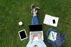 Punto di vista superiore della donna con il computer portatile che si siede sull'erba verde Immagine Stock Libera da Diritti